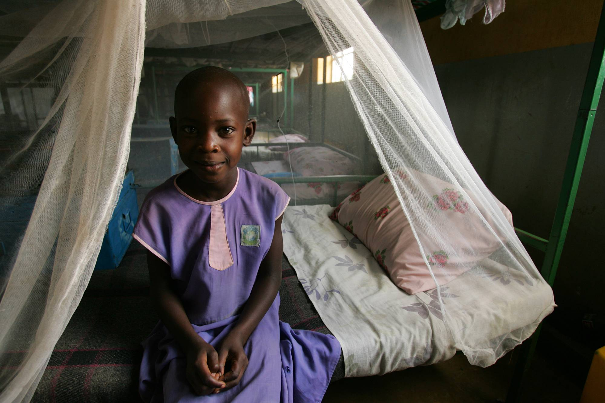 a-child-sits-under-a-malaria-net_2000x1333